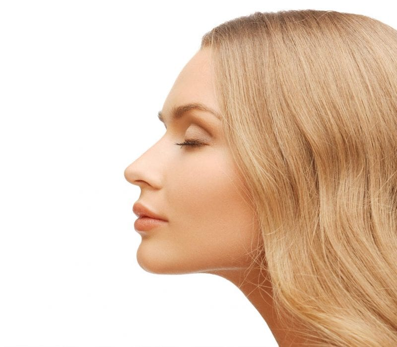 A profile view of a blonde lady with her eyes closed